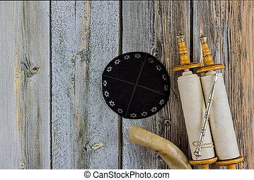 Jewish Orthodox prayer items kippa on a shofar, torah scroll