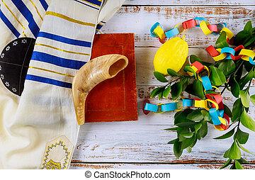 Jewish ritual festival of Sukkot in the jewish religious symbol over paper colorful chain garland praying book kippah tallit