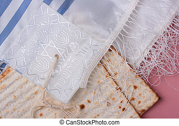 Two pieces of matzah laying next to a blue and white tallit.