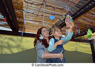 Jewish woman and child decorating their family Sukkah for...
