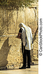 Unidentified jewish worshiper in tallith and tefillin praying at the Wailing Wall an important jewish religious site. Jerusalem. Israel
