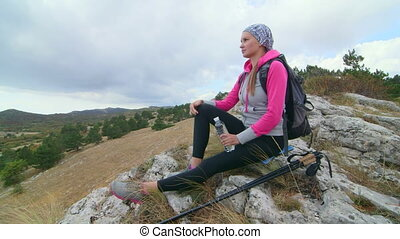 JIB CRANE: Fit young woman day hiker on top of mountain...
