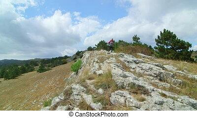 JIB CRANE: Woman day hiking highlands walking along bare...