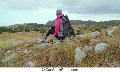 JIB CRANE: Woman hiker with backpack relaxing on top of mountain plateau