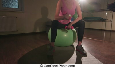 JIB CRANE: Young woman exercising at fitness club with...