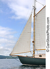 Jib, Foresail, and Wooden Mast of Schooner Sailboat on a Sunny Summer Day