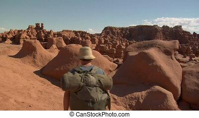 jib shot as man climbs over rocks in goblin Valley Utah