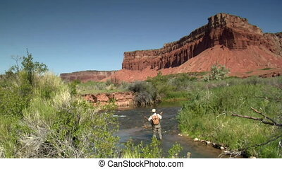 jib shot of fly fisherman and red rock cliffs