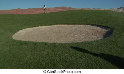 jib shot of man putting on desert golf course