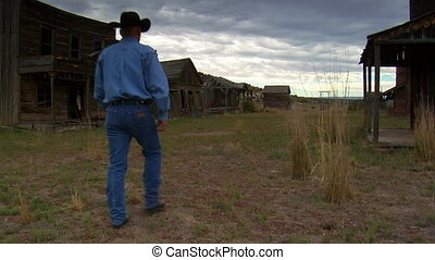 jib shot up as cowboy walks through old West movie set
