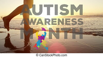 Jigsaw forming a ribbon and autism awareness month text against woman walking on the beach