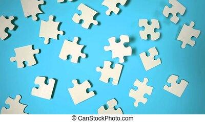 Jigsaw puzzle falling on blue surfa