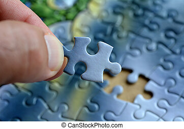 Jigsaw puzzle - Hand holds the last puzzle piece. Business ...