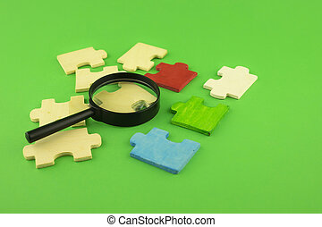 Jigsaw puzzle pieces with magnifying glass