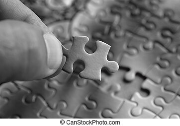 Jigsaw puzzle - Hand holds the last puzzle piece.Business...