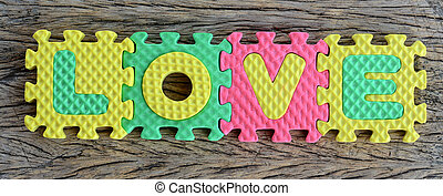 jigsaw written love word on wood background