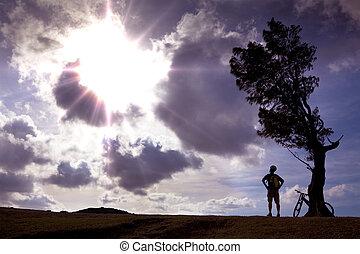 jinete de la bicicleta, estante, en, el, colina, mirar, el, luz del sol, y, relajar