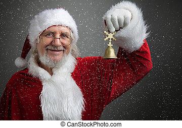 Jingle bells. Santa Claus holding metal bell in his hand