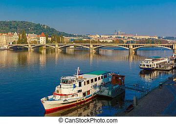 Picturesque view of the boats on Vltava River, Jiraskuv bridge and Prague Castle in Prague, Czech Republic
