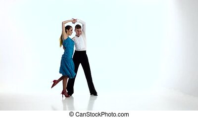 Jive dancing couple of professional elegant dancers,slow motion. White studio