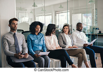 Job applicants sitting in an office waiting for interviews