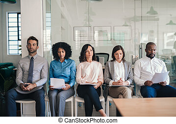 Job applicants sitting together in an office waiting for interviews