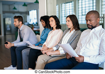 Job applicants waiting in an office for their interviews