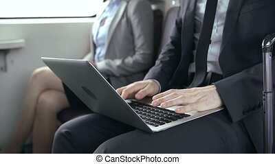 Low section of two people sitting in train coach, focus on unrecognizable man working at portable computer