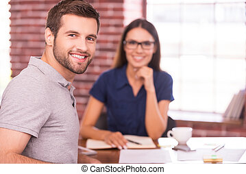 Job candidate. Handsome young man sitting at the table and looking over shoulder with smile while cheerful woman sitting in front of him