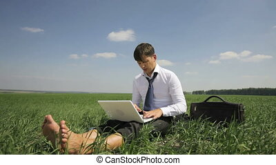 Job climate - Handsome businessman working on his laptop in...