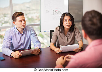Job interview in process - Couple of Latin people with ...