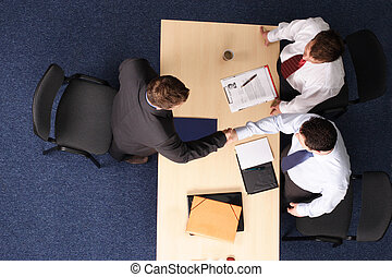 A young man at a a job interview with two interviewers, showing them his resume. Aerial shot taken from directly above the table.