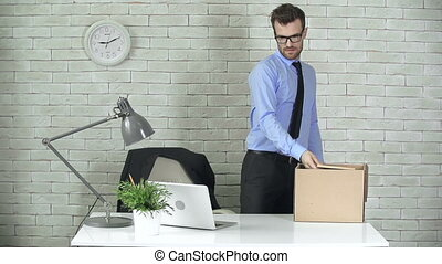 Job Loss - Close up of upset employee packing his things to...