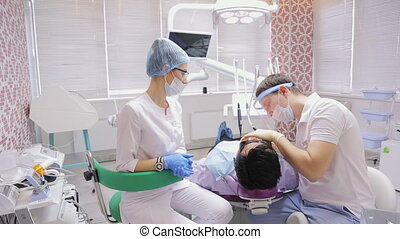 Job of a dentist is paired with a nurse in dental office over lying in a chair by patient.