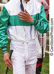 Jockey detail after the race. Hippodrome background. Racehorse