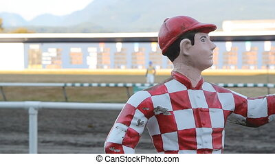 Statue of jockey with horses racing in the background.
