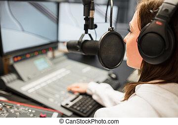 Jockey Wearing Headphones While Using Microphone In Radio Statio