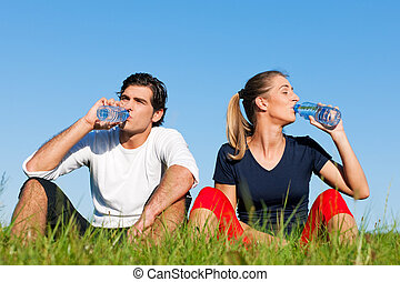 Jogger couple resting and drinking water