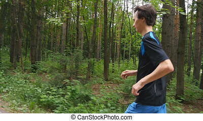 jogger on a trail in the forest in slow motion
