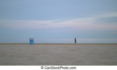 Jogger running beside the sea on a cold day - Wide shot of a...