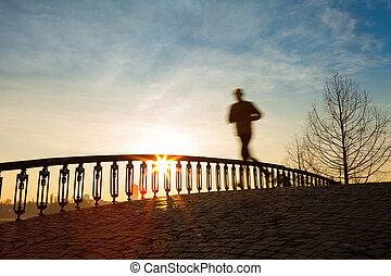 jogger running in sunrise over bridge