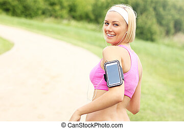 Jogger with smartphone in the park