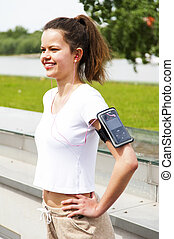 Jogging girl in the city listing music by headphones