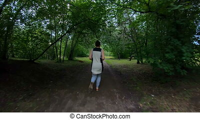 Jogging in the park. Girl running along the forest path. Slow motion