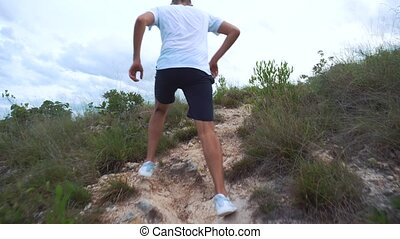 Jogging man on mountain road. Sport fitness boy exercising outside in mountain. Living healthy lifestyle.