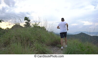 Jogging man on mountain road. Sport fitness boy stumble on mountain trail. Beautiful mountainous view