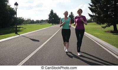Positive smiling adult female riends in activewear jogging in park road on sunny day. Attractive senior female runners running parkway in sportswear. Slow motion. Stedicam stabilized shot.