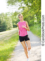 jogging - Young blond woman jogging on pathway in park