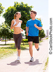 Jogging together.  Full length of young woman and man in sports clothing running along the road