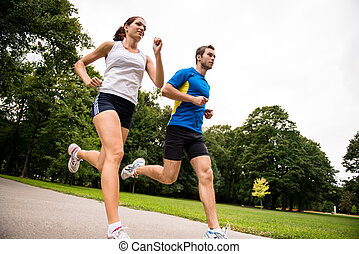 Jogging together - sport young couple - Low angle photo of ...
